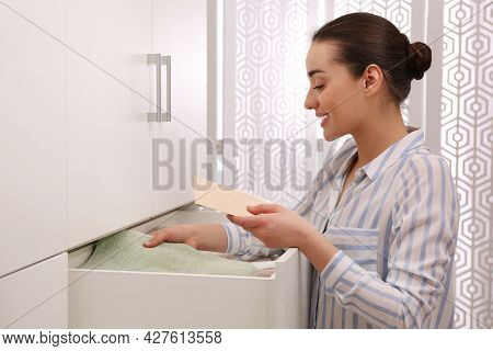 Woman Putting Scented Sachet Into Drawer With Towels Indoors