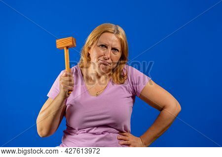 Pretty Middle Aged Woman Posing With A Kitchen Wooden Mallet Isolated On Blue Studio Background.