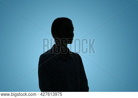 Silhouette Of Anonymous Woman On Light Blue Background