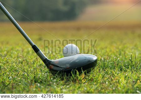The Golf Club And Golf Ball Close Up In Grass Field With Sunset. Golf Ball Close Up In Golf Coures A