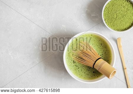 Green Matcha Tea, Powder And Bamboo Whisk On A Gray Concrete Background. Cooking Matcha Tea Close Up