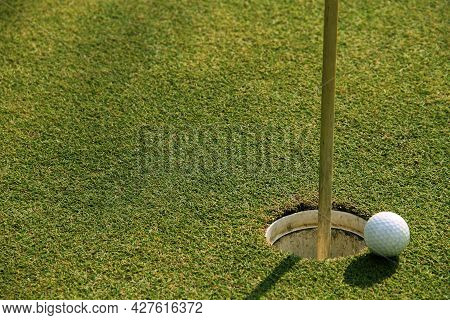 Golf Ball Close Up On Green In Grass Field With Sunset. Golf Ball Close Up In Golf Coures At Thailan