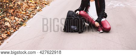 Young Woman In Black Leather Jacket Sitting In The Middle Of The Road With Black Backpack On The Bac