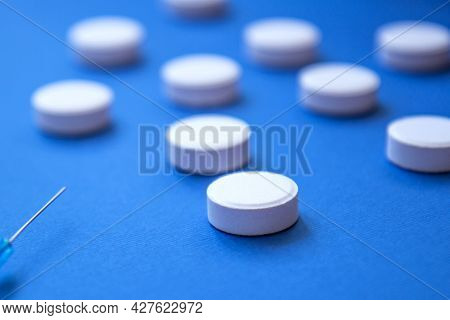Set Of White Pills And A Syringe Needle On Blue Background. Pills Background. White Tablets On A Blu