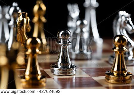 Gold And Silver Chess Figures Placed On Wooden Chessboard. Intellectual Duel And Tactical Battle In