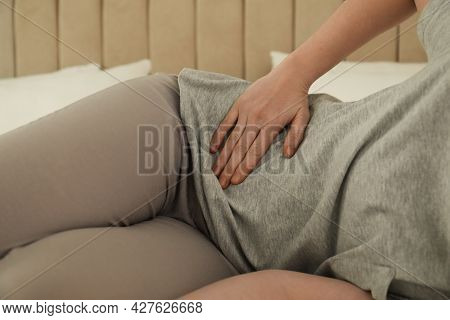 Woman Suffering From Appendicitis Inflammation At Home, Closeup