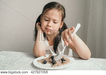 The Girl Doesnt Want To Eat Porridge. The Child Is Capricious And Refuses To Eat. The Baby Picks At