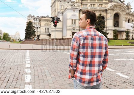 Young Man Waiting To Cross Street, Back View. Traffic Rules And Regulations