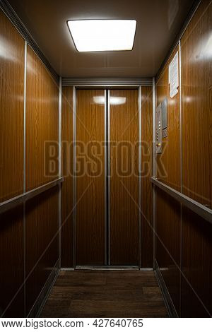 Interior Inside A Closed Clean Old Soviet Elevator Car Lined With Wood.