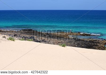 View Of The Horizon From The Shore With White Sand And Rocks, A Lone Fisherman And Sparcling Blue Oc