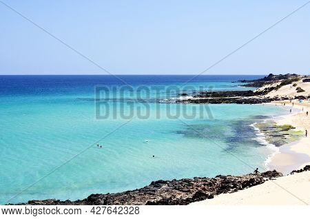 View To The Horizon From The Beach With White Sand And Rocks And Transparent, Sparkling Blue Ocean W