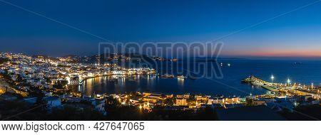 Beautiful Night Panorama Of Mykonos, Greece, Ships, Port, Whitewashed Houses. Town Lights Up. Vacati