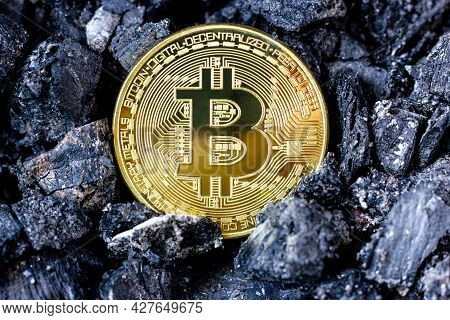 Gold Bitcoin Coin On A Black Coal Background. Cryptocurrency Mining. Btc Cryptocurrency. The First C
