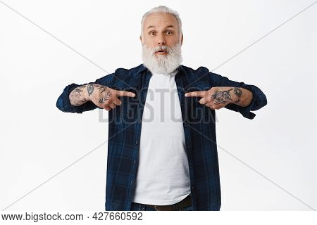 Surprised Senior Bearded Man With Tattoos, Pointing At Himself And Gasping Amazed, Being Chosen, Hea