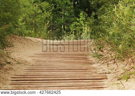 Wooden Footbridge To The Beach By The Sea. The Sandy Beach Has A Wooden Walkway To The Sea. Tourist