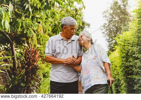 Senior Couple, A Strong Relationship, Lasting Forever : Elderly Couple Walking In The Shady Front Ga
