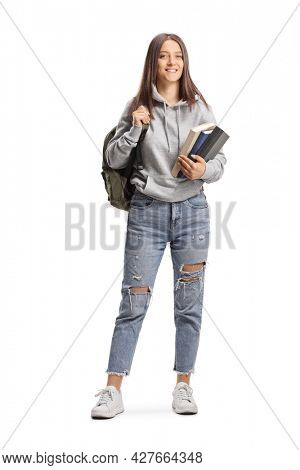 Full length portrait of a female student with a cap holding books and backpack isolated on white background