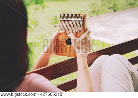 Back View Asian Woman Enjoys A Kalimba, Or Thumb Piano, An African Traditional Instrument In Her Gar