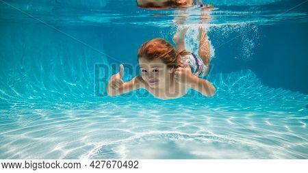 Underwater Child Swim In Water Swimming Pool. Summer Activity And Healthy Kids Lifestyle. Summer Vac