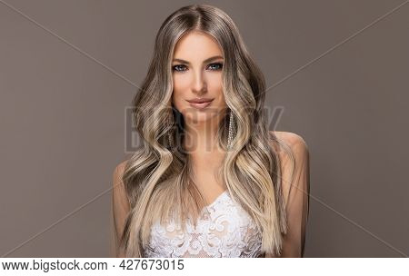 Beautiful Girl  Hair Coloring In Ultra Blond. Stylish Hairstyle Curls Done In A Beauty Salon. Fashio