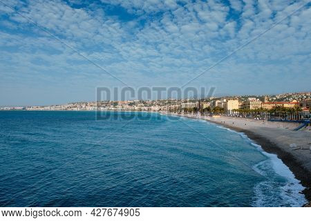 Picturesque scenic view of Mediterranean sea coast in Nice, France. Mediterranean Sea waves surging on the coast, people are relaxing on the beach. Nice, France