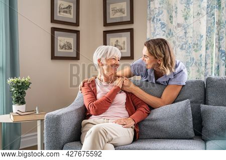 Smiling adult daughter embracing from behind old mother sitting on sofa and laughing together. Aged woman having fun with mature daughter during home visit. Old mom feeling happy with daughter.