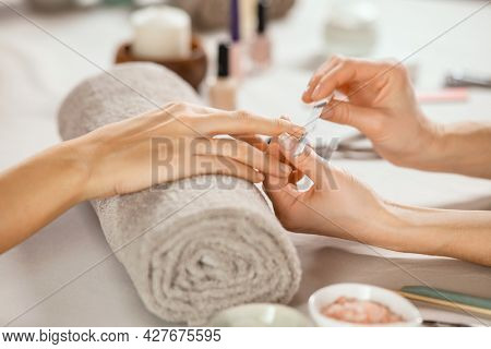 Close up shot of a woman in a nail salon receiving manicure by beautician with metal nail file. Woman getting nail manicure at spa centre. Beautician file nails to a customer in luxury salon.