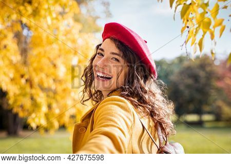 Happy girl holding hand and looking behind while walking in the park. Beautiful woman relaxing at the park wearing winter clothing. Young smiling woman pulling her boyfriend and looking at camera.
