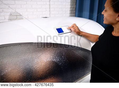 Woman Inside A Spa Capsule. Beautician Adjusting Programs In Spa Capsule. Spa Capsule Is The Perfect