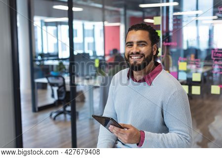 Portrait of mixed race male creative worker using tablet computer and smiling. modern office of a creative design business.