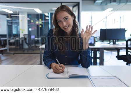 Portrait of caucasian female creative worker sitting at desk looking at camera. modern office of a creative design business.