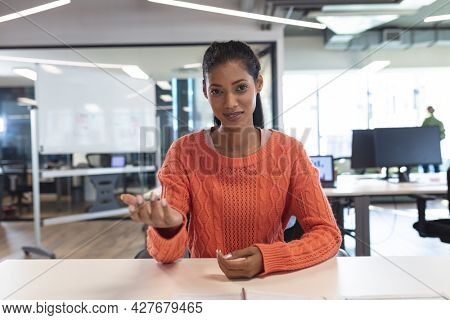 Portrait of mixed race female creative worker sitting at desk looking at camera. modern office of a creative design business.