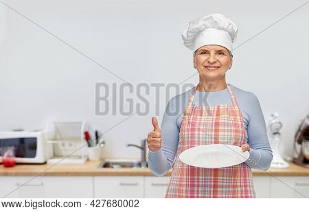 cooking, culinary and old people concept - portrait of smiling senior woman or chef in toque in apron holding empty plate showing thumbs up over kitchen background