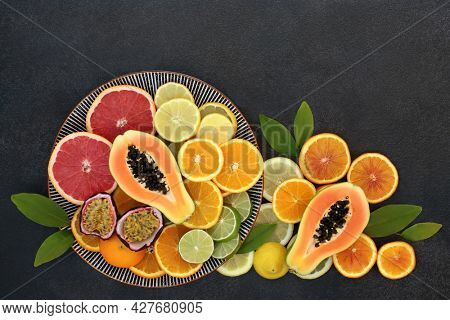 Tropical and citrus fruit collection for high fibre boost high in antioxidants, fibre, anthocyanins, lycopene, vitamins and minerals. Immune system boosting healthcare concept. Flat lay on slate.