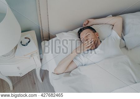 Young Sleepy Man Waking Up In Morning After Night Sleep While Lying In Bed, Yawning And Covering His