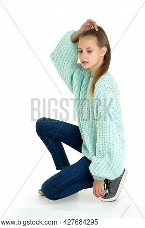 Smiling Teenage Girl Crouching On Floor. Beautiful Girl Wearing Fashionable Outfit Sitting On One Kn