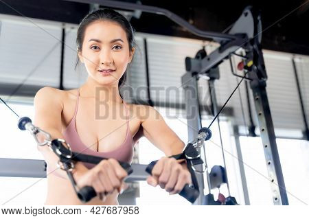 Beautiful Fitness Slim Fit Woman In Sportswear Working Exercise With With Cable Crossover Machine In