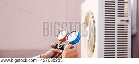 Air Condition Mechanic Using Manifold Gauge For Filling Home Air Conditioner And Checking Maintenanc