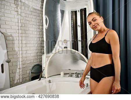 Pretty Young Woman Stands Near Modern Spa Equipment - Spa Capsule For Non-invasive Anti-aging, Anti-
