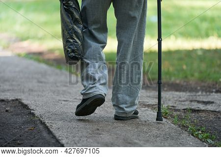 An Elderly Man Slowly Walks Along The Path Leaning On A Cane. In His Hand He Holds A Plastic Bag Wit