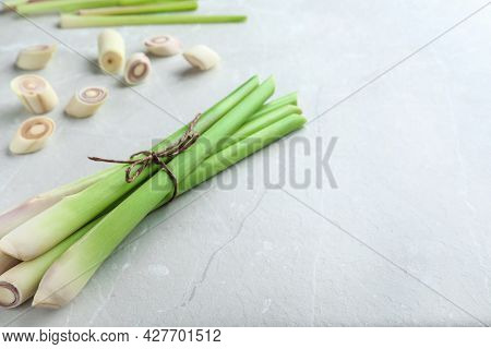 Whole And Cut Fresh Lemongrass On Light Table. Space For Text