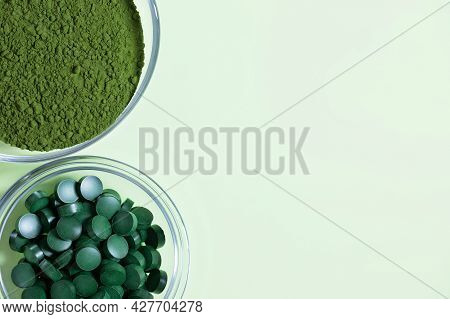 Chlorella Powder And Spirulina Tablets On A Green Background. Organic Food Supplement. View From Abo