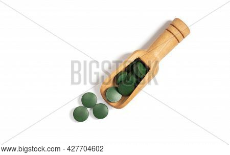 Spirulina Green Pills In A Wooden Spoon Isolated On A White Background. Chlorella Tablets. Top View,