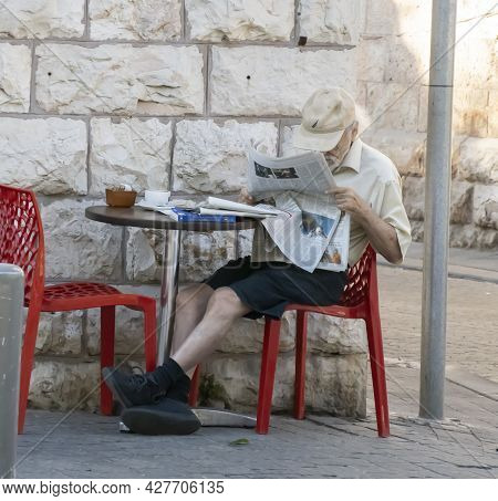 Jerusalem, Israel - July 21st, 2021: A Senior Citizen Reading A Newspaper In A Coffee Shop On A Jeru