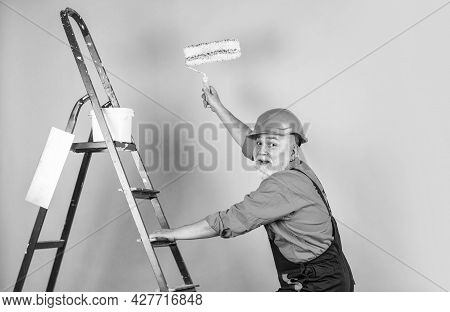 Man In Working Clothes Painting Wall In Empty Room. Painter In Overall And Cap With Paint Bucket. Bu