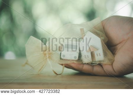 Hand Holds A Gold Transparent Bag With Toy Car And Model House. The Concept Of Buying Real Estate, R