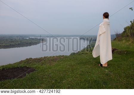 A Young Girl Stands On A High Cliff, Green Grass. The Girl Wrapped Herself In A Warm White Blanket A