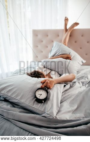 Young Woman With Alarmclock Lying With Legs Up On The Bed At The Morning. Early Wake Up, Not Getting