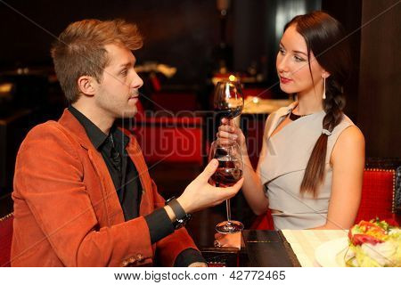 Man and woman with a glass of wine looking lovingly into the eyes