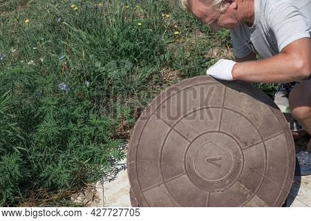 The Man Opens The Manhole Cover Of The Water Well. Checking And Fixing Water Metering.